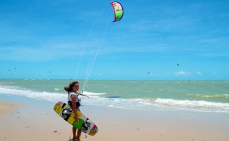 Young woman standing on beach with kiteboard and kite in Cumbuco, Brazil