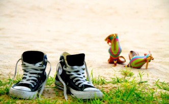 Converse sneakers and salsa shoes in the sand
