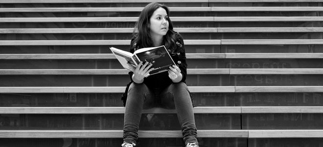 Woman sitting on stairs with book