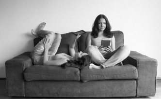 Women reading in Kindle on couch