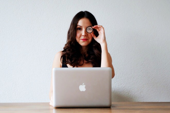 Woman sitting behind laptop with monocle