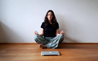 Woman meditating with laptop in front