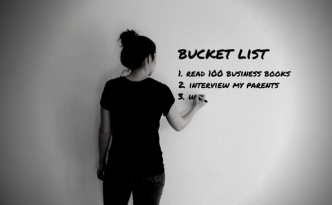 Young woman writing bucket list on wall