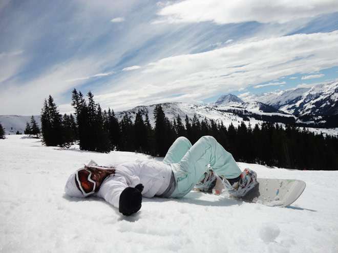 female snowboarder lying down on snow