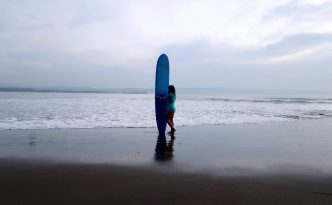Mirha Masala holding blue surfboard upright on beach