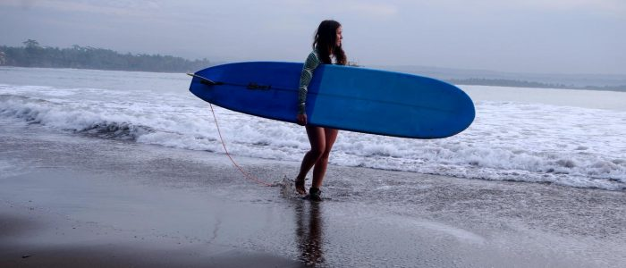 Mirha Masala walking with surfboard on beach